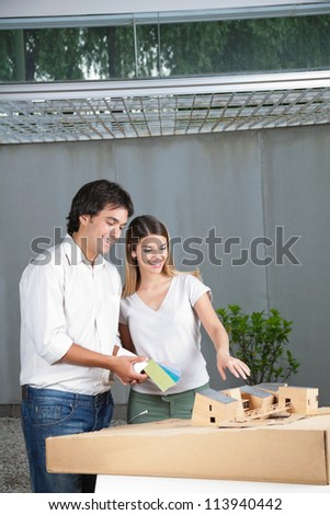 Female architect showing model house while colleague holds color swatches