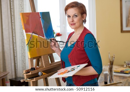 female artist painting in her living room - stock photo