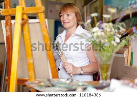 Female artist paints a picture on canvas with oil paints - stock photo