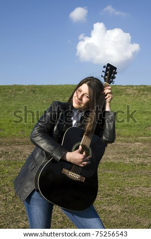 Female artist performer in love with her acoustic guitar - stock photo