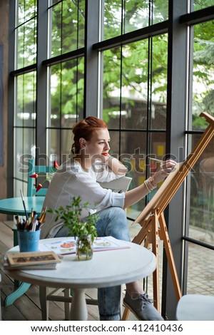 Female Artist Working On Painting In Bright Daylight Studio - stock photo