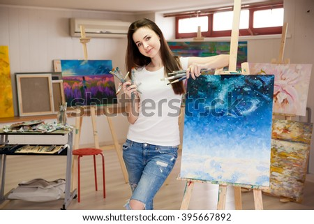 Female Artist Working On Painting In Studio - stock photo