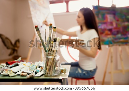 Female Artist Working On Painting In Studio. Background image, selective focus on  foreground - stock photo