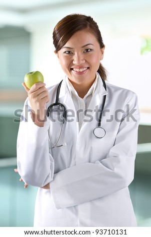 Female Asian doctor holding an apple. Healthy eating concept. - stock photo