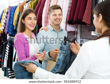Female assistant serving smiling customers asking in clothing boutique