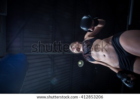 Female Athlete boxer punching a punching bag with dramatic edgy lighting in a dark studio