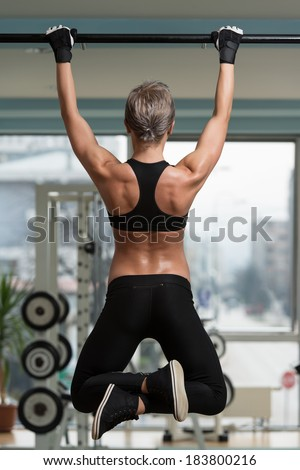 Female Athlete Doing Pull Ups - Chin-Ups In The Gym - stock photo