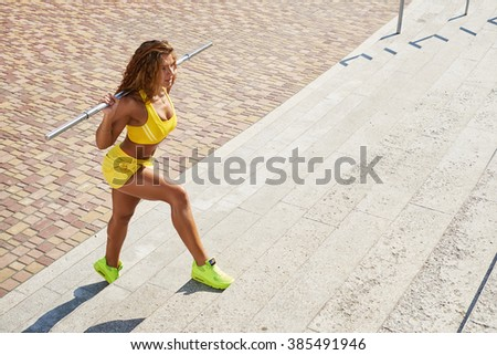 Female athlete doing squats with crossbar - stock photo