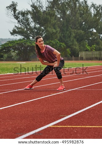 Female athlete doing stretches on running track