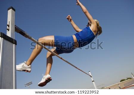 Female athlete high-jumping - stock photo