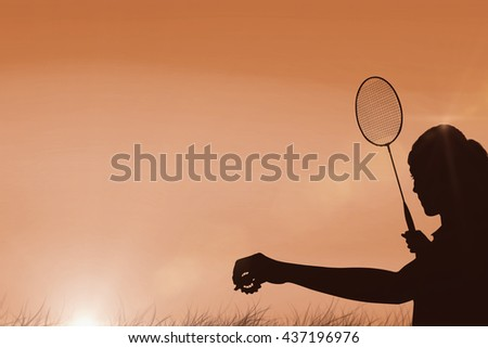 Female athlete holding a badminton racquet ready to serve against sun rising - stock photo