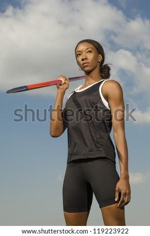Female athlete holding javelin - stock photo