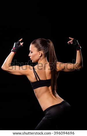 Female athlete in aesthetic pose. Fit woman posing on stage. Personal trainer showing her form. Beauty of modern sport. - stock photo