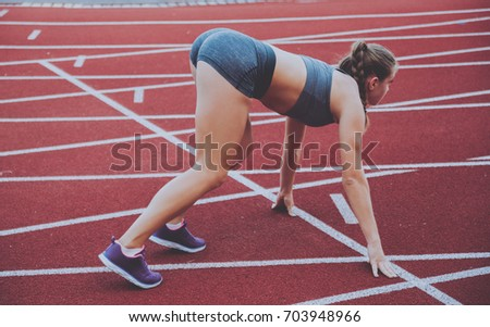 Female athlete in position ready to run. Young woman ready for a sprint.