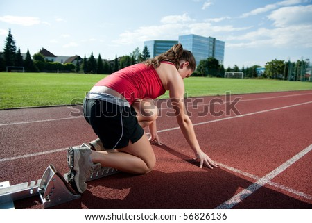 Female athlete in the starting block, getting ready to go - stock photo