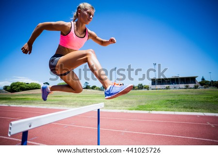 Female athlete jumping above the hurdle during the race - stock photo