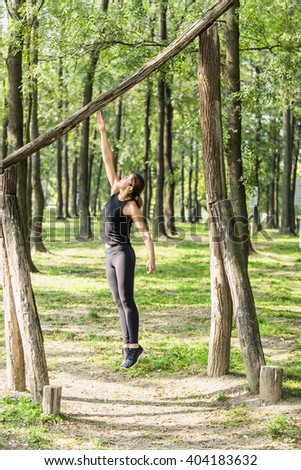 Female athlete jumping during fitness trail exercise - stock photo