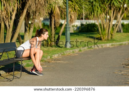 Female athlete lacing running shoes and getting ready for  outdoor training in a park. Woman tying sport footwear laces before fitness exercising. - stock photo