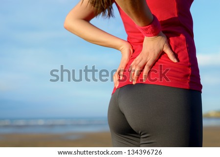 Female athlete lower back painful injury. Caucasian fitness girl gripping her lowerback because sport injury after exercising and running. - stock photo
