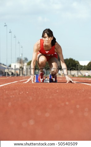 Female athlete on starting block - stock photo