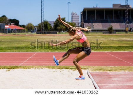 Female athlete performing a long jump during a competition - stock photo