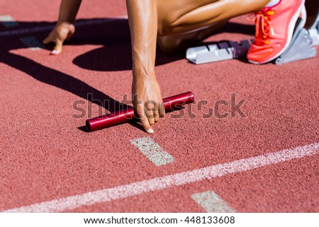 Female Athlete Ready To Start The Relay Race On Running Track