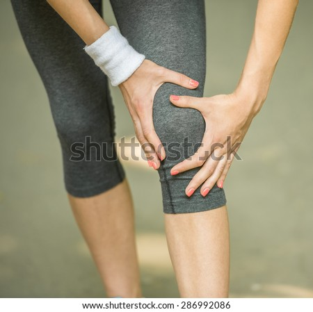 Female athlete runner touching foot in pain due to sprained ankle. - stock photo