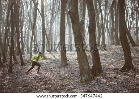 Female athlete running in the forest trail