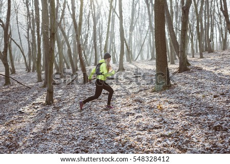Female athlete running in the forest trail. Outdoor sport concept.