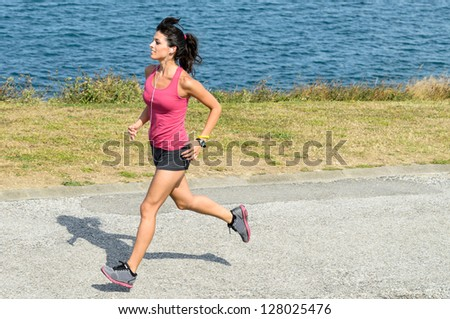 Female athlete running on summer. Female caucasian fitness woman jogging on sea background. - stock photo