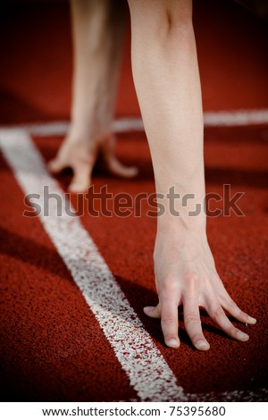 Female athlete's arms on the starting line. High contrast. - stock photo