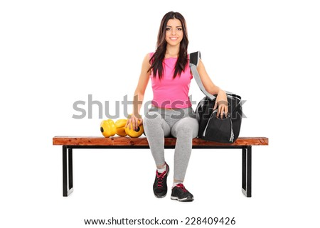 Female athlete sitting on a bench with her training equipment isolated on white background - stock photo