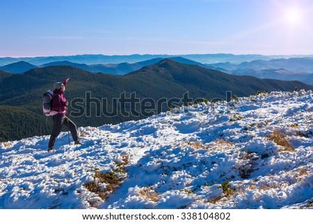 Female Athlete Sport Clothing carrying Backpack Walking Up Mountain Peaks Sunlight Sky Majestic Summits Sun Shining Background - stock photo