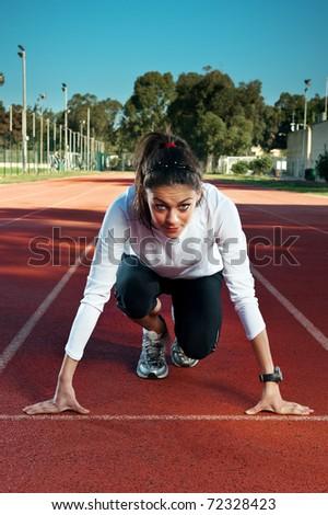 Female athlete/sprinter in 'on your marks, get set, go' starting starting position. - stock photo