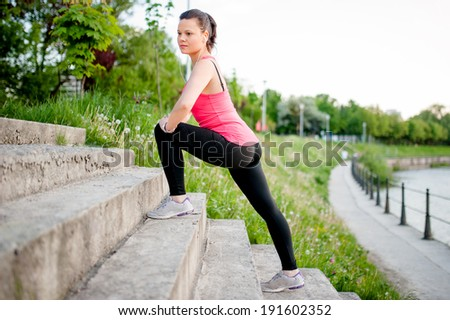 Female athlete stretching and running along a river at dusk - stock photo