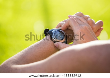 Female athlete tracking her activities using heart rate monitor, outdoors