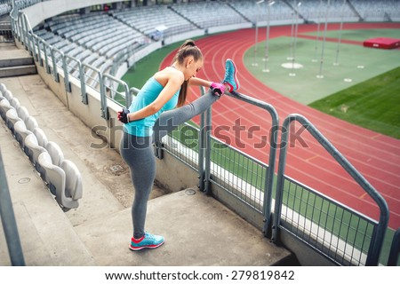 Female athlete training and stretching for warming up on the stairs. Fitness girl training and running - stock photo