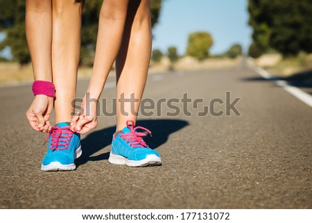 Female athlete tying sport shoes laces for running on road. Runner getting ready for training. - stock photo