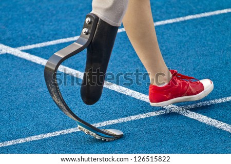 female athlete with handicap is crossing the line - stock photo