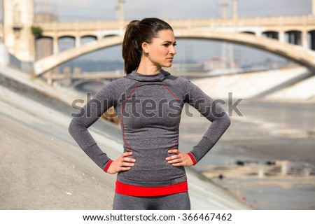 Female athlete women's sportswear fit thin physique athletic build outdoor city bridge confident powerful - stock photo