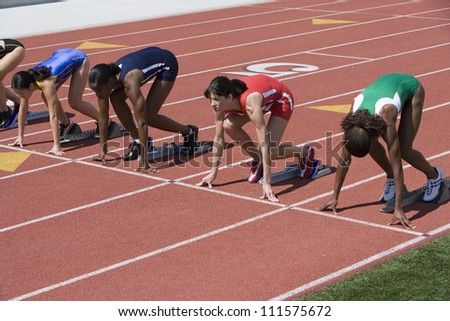 Female athletes at starting line on race track - stock photo