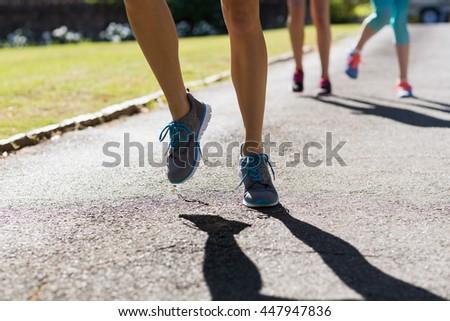 Female athletes feet running on running track in park - stock photo
