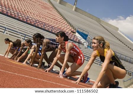 Female athletes on race track - stock photo