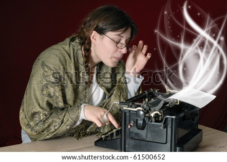 female author typing on an old typewriter on dark red background - stock photo