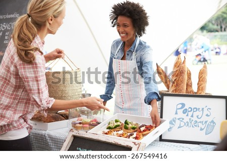 Female Bakery Stall Holder At Farmers Fresh Food Market - stock photo