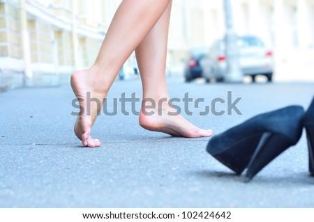 female bare feet dancing on summer street - stock photo