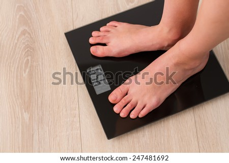 female bare feet standing on a black mirror scales - stock photo