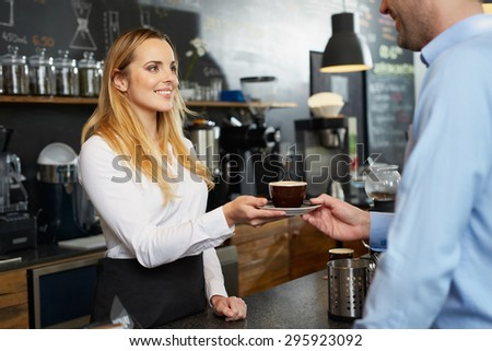Female barista offering a cup of cappuccino to customer at cafe - stock photo