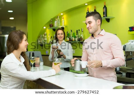 Female bartender and male barista working at bar. Focus on man - stock photo