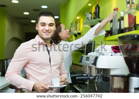 Female bartender and smiling male barista working at bar. Focus on man - stock photo